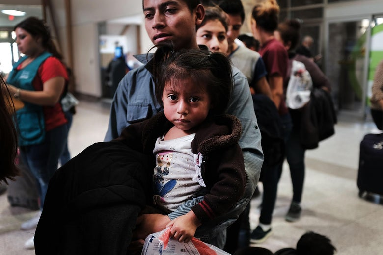 A Guatemalan father and his daughter arrives with dozens of other women, men and their children at a bus station following release from Customs and Border Protection on June 23, 2018 in McAllen, Texas.