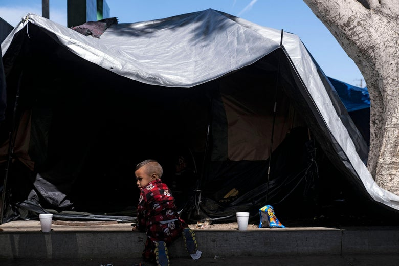 A migrant child plays near a tent at a migrants camp where asylum seekers wait for US authorities to allow them to start their migration process outside El Chaparral crossing port in Tijuana, Baja California state, Mexico on March 17, 2021.