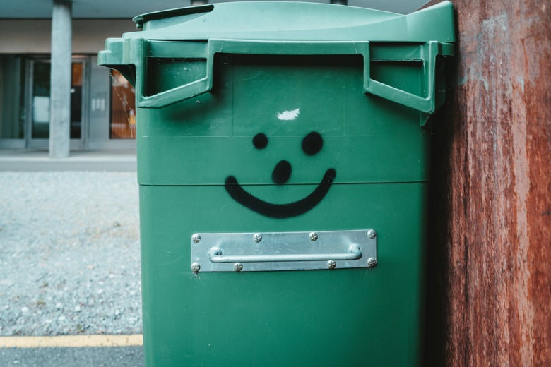 A green trash bin with a smiley face on it.