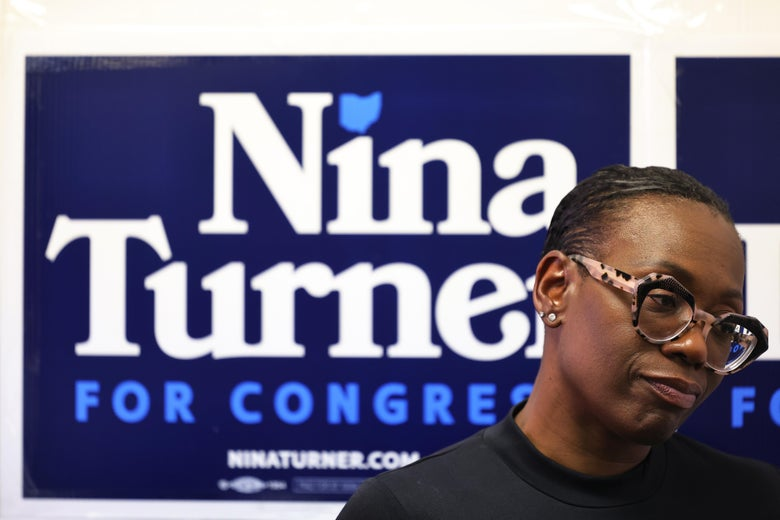Nina Turner standing in front of a campaign sign.
