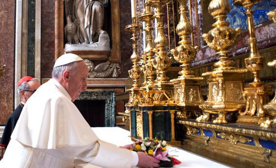 Pope Francis placing flowers on an altar