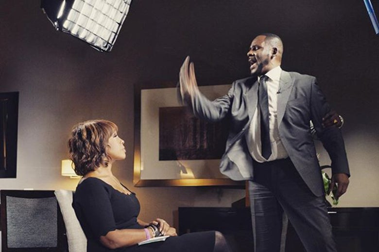 R. Kelly, who has just stood up mid-interview, making an angry gesture at Gayle King, who is seated and looking at him skeptically.