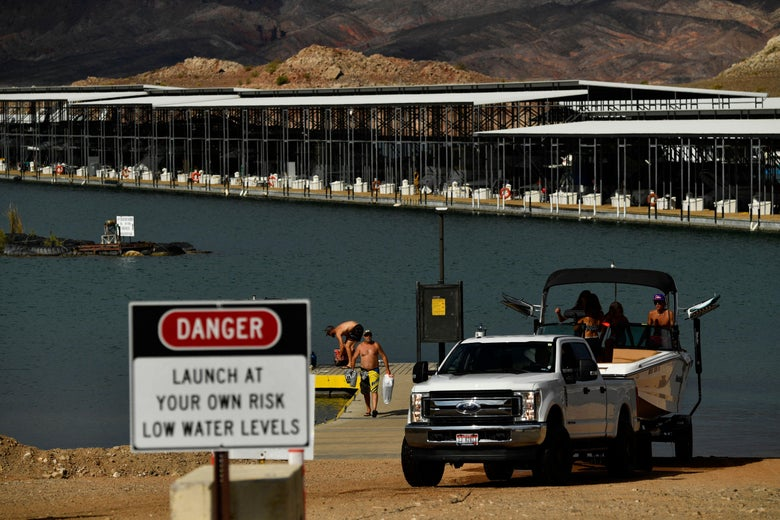 """Visitors remove a boat from a boat ramp near a sign that says """"DANGER. Launch at Your Own Risk. Low Water Levels."""""""