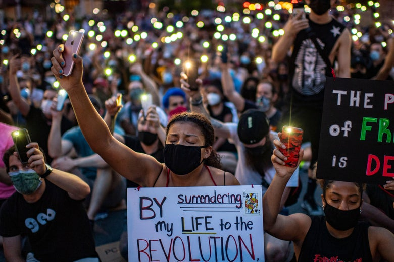 Protesters wearing masks hold up their phones with the flashlights turned on.