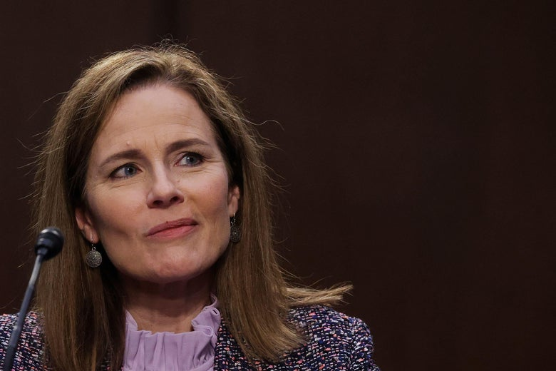 Amy Coney Barrett smirks and looks up and to her left.