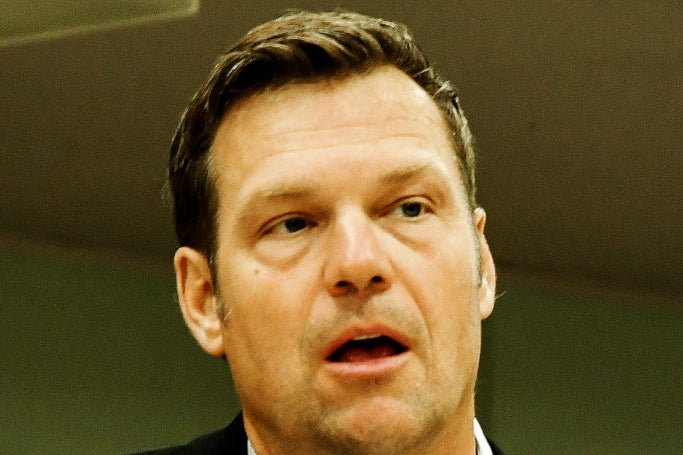 A close-up on Kansas Secretary of State Kris Kobach's face in which his mouth is open and he looks silly.