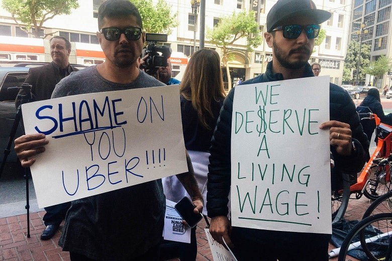 "Protesters holding signs reading ""SHAME ON YOU UBER"" AND ""WE DESERVE A LIVING WAGE."""