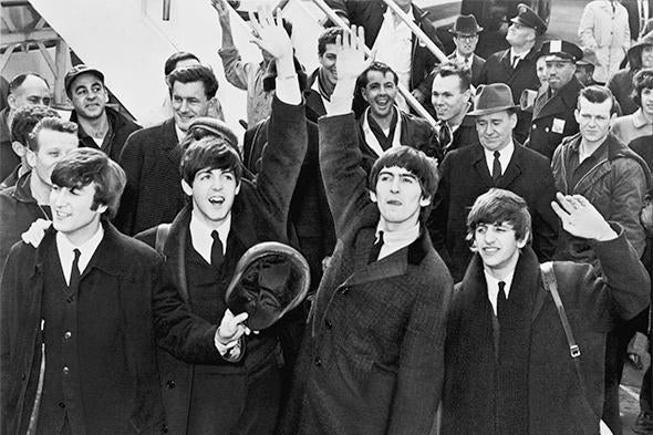 The Beatles standing in a crowd waving to fans.
