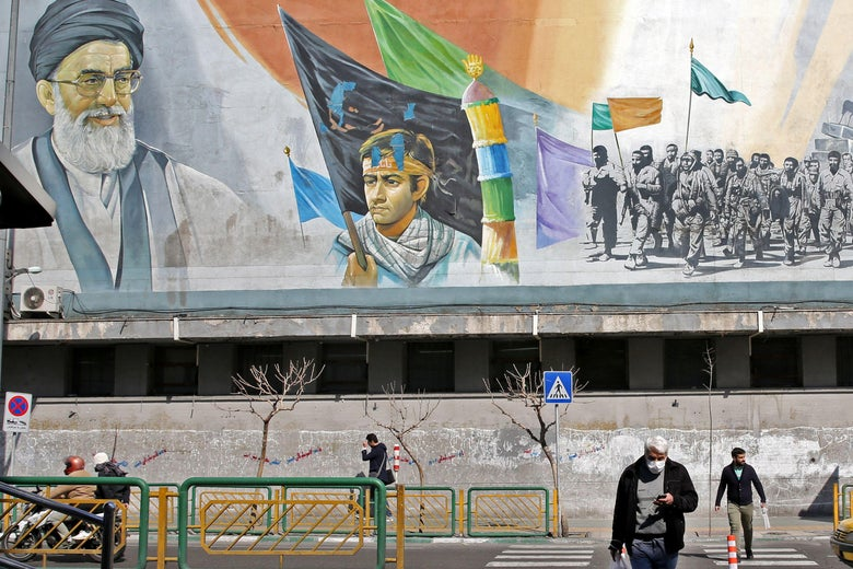 Men in masks walk near a mural featuring an image of  Ayatollah Ali Khamenei.