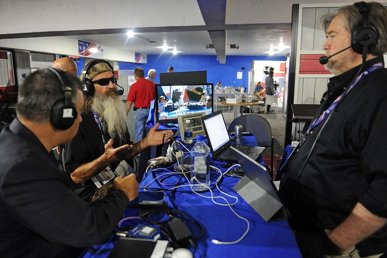 Bossie, a broad-shouldered man with short graying black hair, sits at a table in a bustling media room with the long-bearded Phil Robertson of Duck Dynasty. Steve Bannon is standing next to the table. All three are wearing headsets for a radio broadcast.
