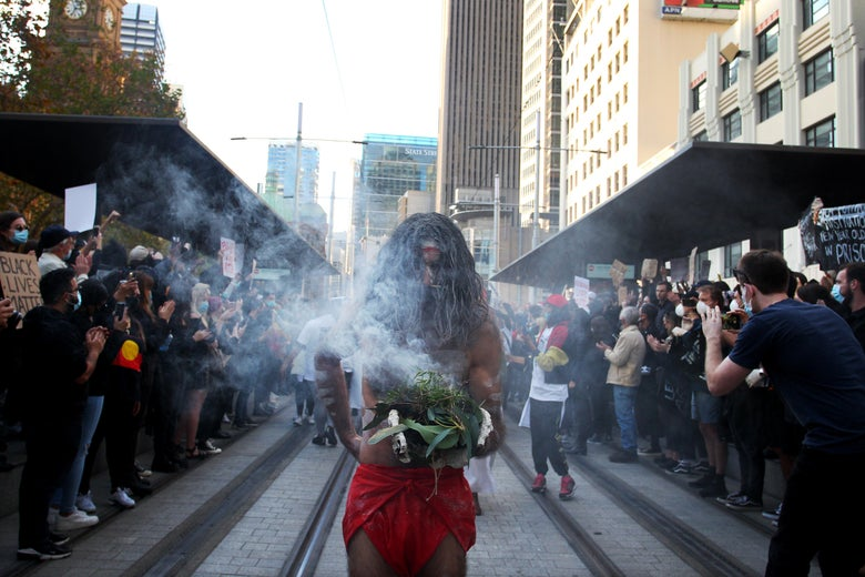 Aboriginal elders conduct a traditional smoking ceremony at Town Hall during a Black Lives Matter protest march on June 6, 2020 in Sydney, Australia.