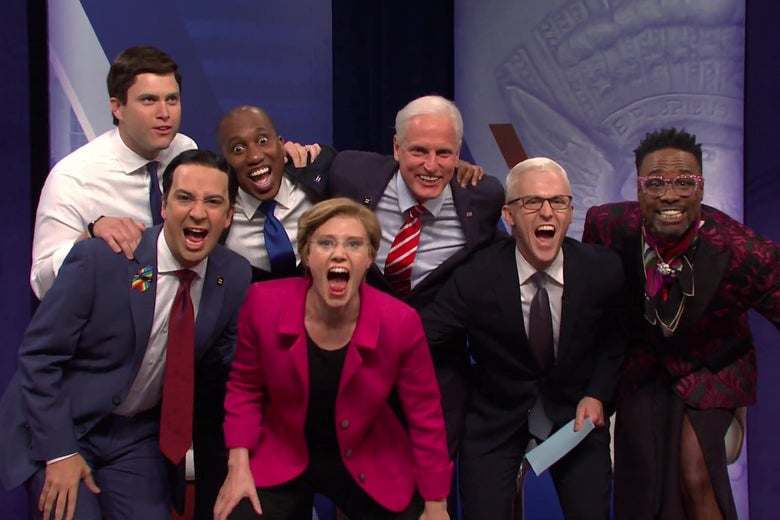 "Colin Jost, Chris Redd, Woody Harrelson, Alex Moffat, Billy Porter, Lin-Manuel Miranda, and Kate McKinnon yelling ""Live from New York, it's Saturday Night!"""