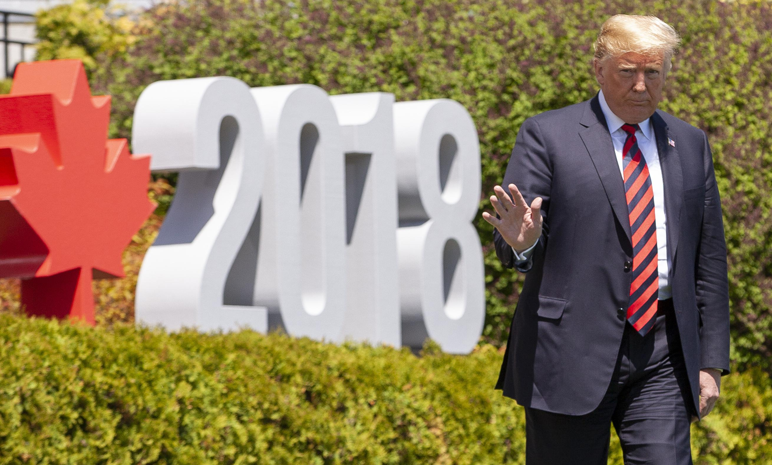 Donald Trump walks by a sign that says 2018 with a red maple leaf.