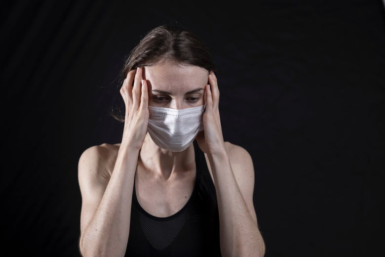 a woman with a face mask putting her face in her hands