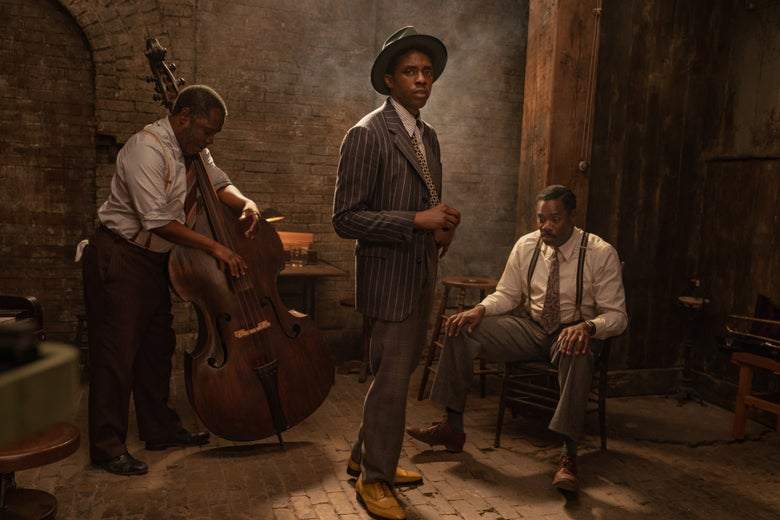Chadwick Boseman stands in a pinstriped suit and fedora, in front of a man with an upright bass and another man seated in a chair.