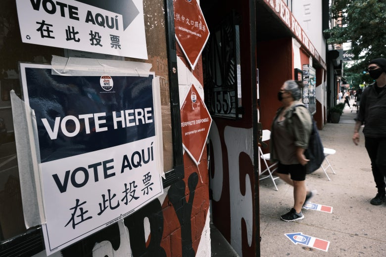 Signs alert people to a voting site in Manhattan as voters stand in line outside to vote.