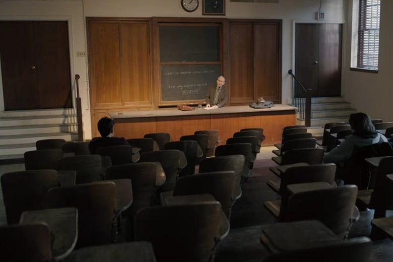 Elliot at the front of a college classroom with old chairs in it.