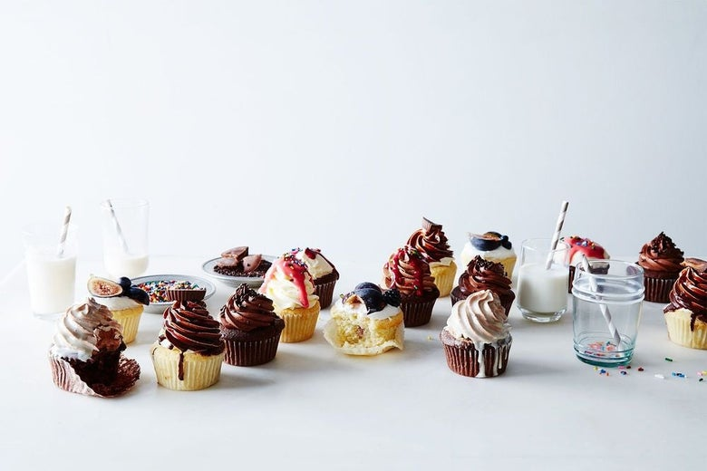 Cupcakes in a variety of cake and frosting flavor combinations with glasses of milk.