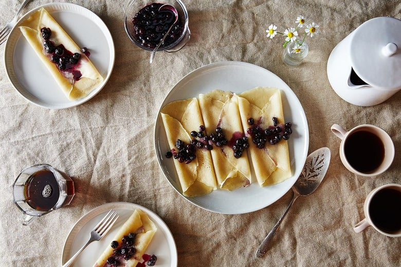 A table laid with plates of folded crepes, topped with berry compote.