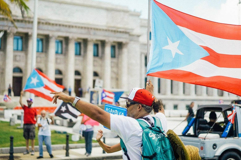 People wave Puerto Rican flags outside the Capitol