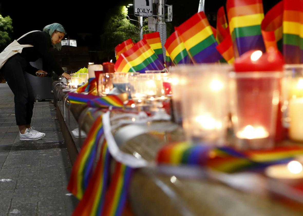 A woman lights a candle during a candlelight vigil for the victims of the Pulse Nightclub shooting in Orlando, Florida.