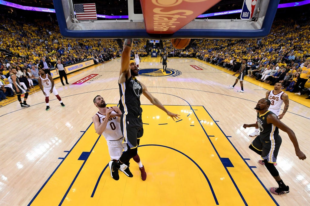 JaVale McGee of the Warriors dunks while Kevin Love watches.