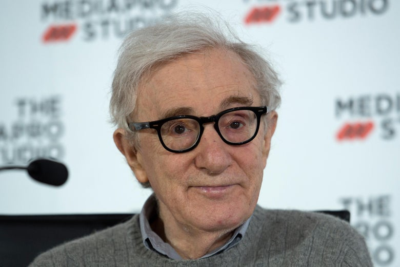 Woody Allen wearing black glasses a gray collared shirt and a gray sweater, in front of a white background with black text.