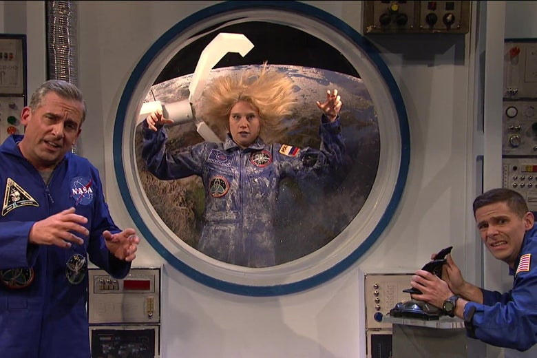 Steve Carell and Mikey Day dressed as astronauts on the International Space Station, as an extremely dead Kate McKinnon floats through space outside their window.
