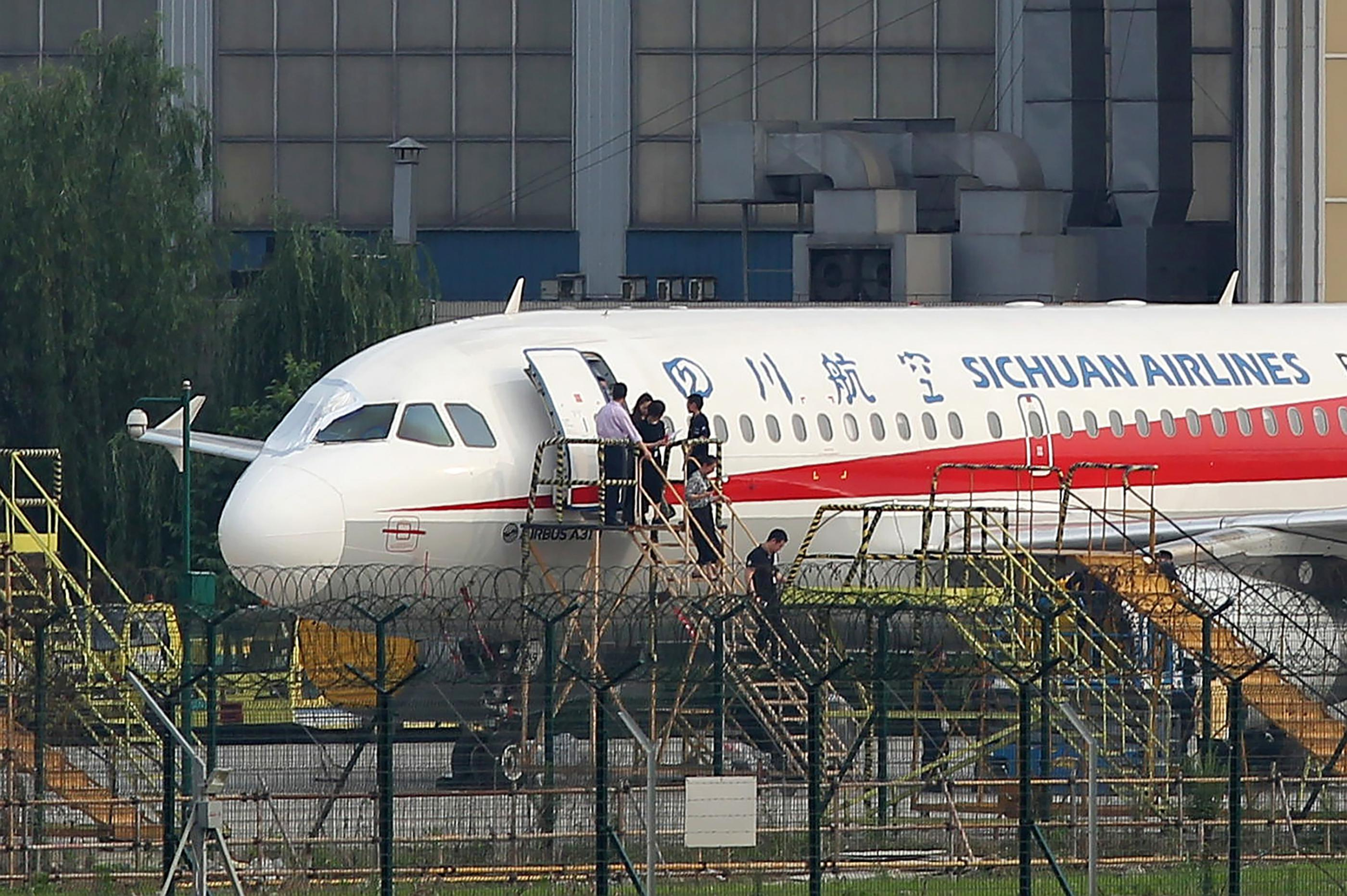 Employees check the Sichuan Airlines Airbus A319.