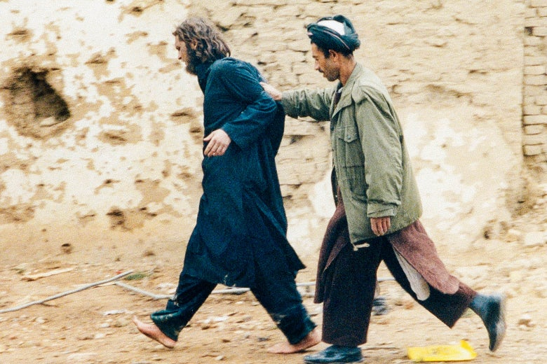 U.S.-born John Walker Lindh is led away by a Northern Alliance soldier near Fort Qala-i-Janghi Prison in Afghanistan on Dec. 1, 2001 after he was captured following an uprising.