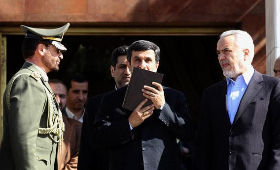 Iranian President Mahmoud Ahmadinejad kisses the Koran.