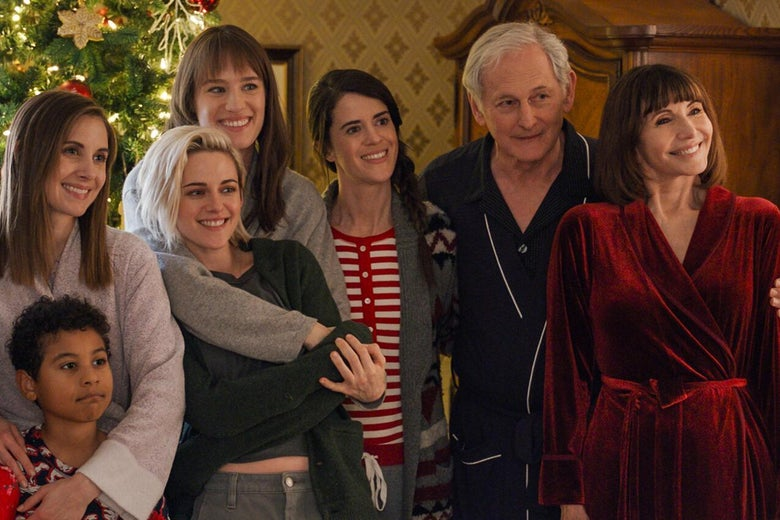 The pajama-clad cast of Happiest Season poses for a Christmas photo by their decorated tree.