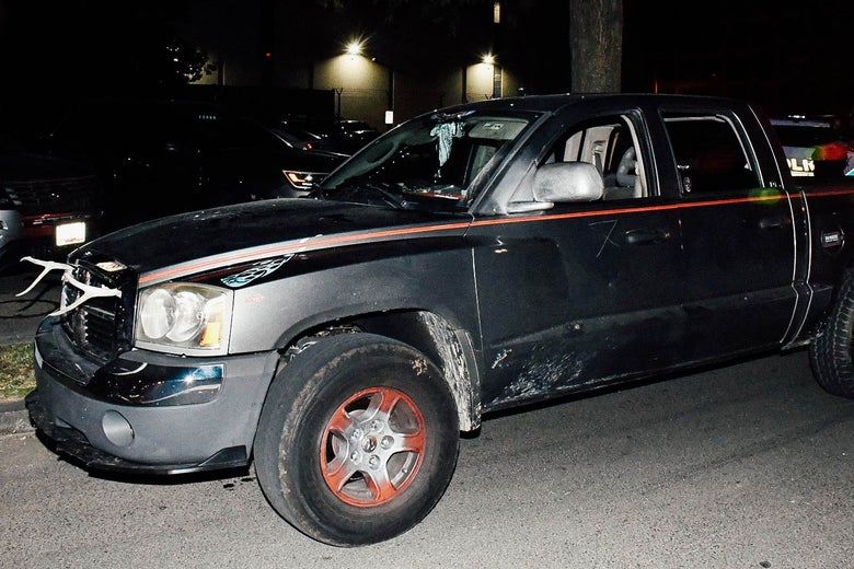 A dilapidated black truck with red piping and what appear to be antlers on its front grille is seen in the glare of a camera flash or spotlight.