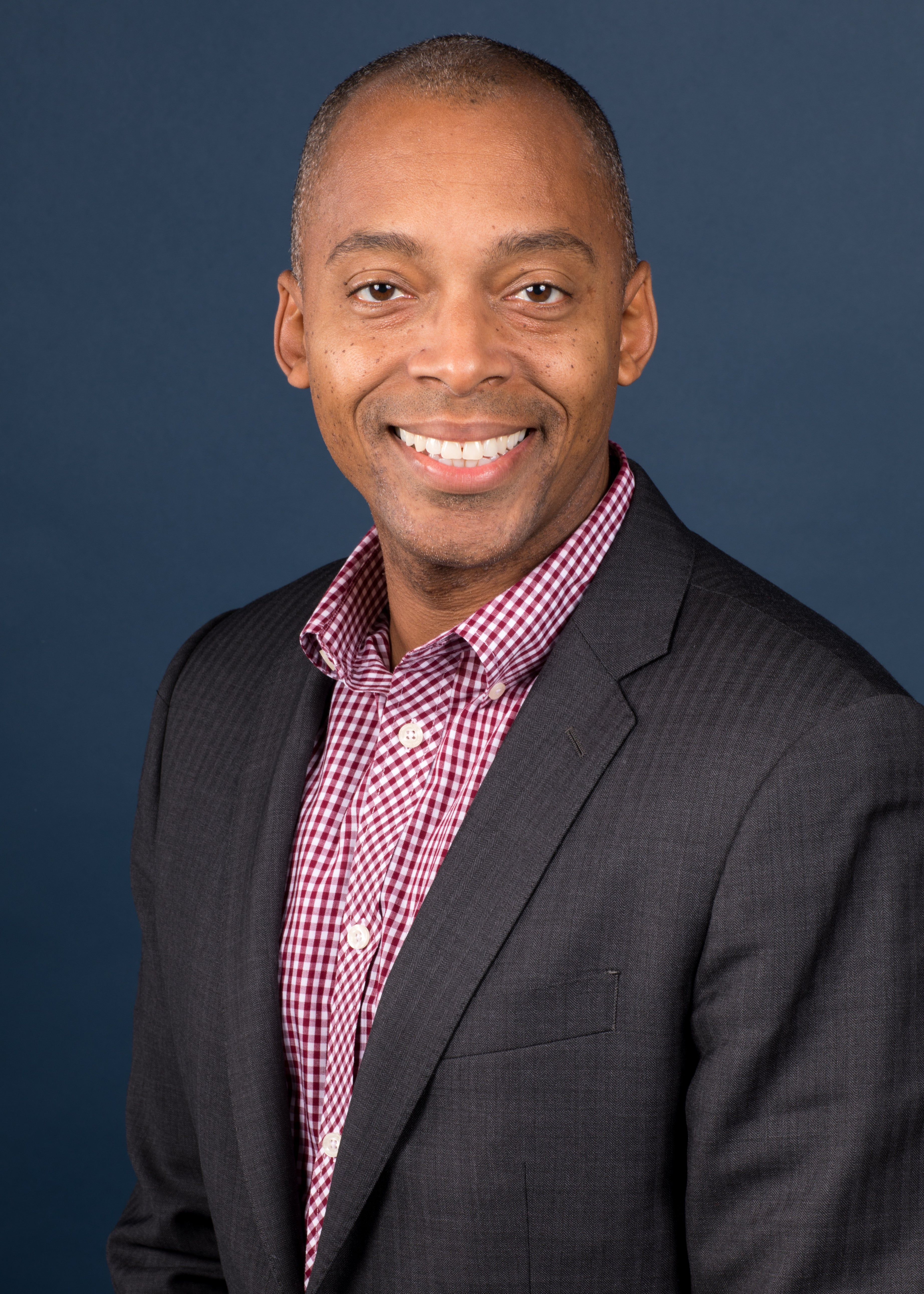 A smiling Black man in a checked shirt and blazer.