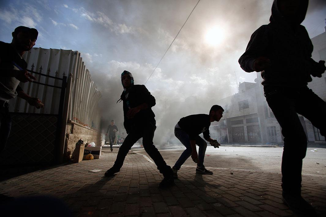 Palestinian protesters prepare to throw stones at Israeli army soldiers during clashes following an anti-Israel demonstration in solidarity with al-Aqsa mosque, in the West Bank city of Hebron on Nov. 14, 2014. Israel and the Palestinians have pledged to take concrete steps to calm tensions around Jerusalem's holiest site, U.S. Secretary of State John Kerry said on Thursday after talks in the Jordanian capital. Violence has flared in recent weeks over the compound, revered by Muslims as Noble Sanctuary, where al-Aqsa mosque stands, and by Jews as the Temple Mount, where their biblical temples once stood.