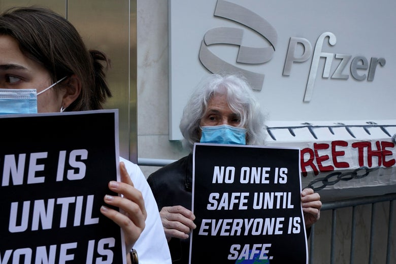 """People hold signs that say """"No one is safe until everyone is safe"""" in front of the Pfizer building in New York"""