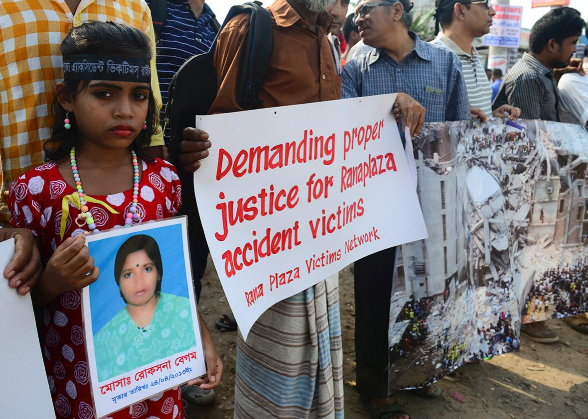 A Bangladeshi girl holds a photo of her mother, who died in the Rana Plaza building collapse, during a protest march on the third anniversary of the disaster at the site where the building once stood in Savar, on the outskirts of Dhaka on April 24, 2016.