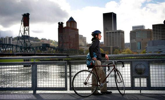 Man with bicycle looking at skyline over river, Portland, Oregon.