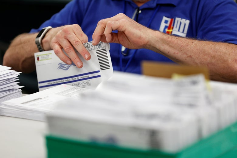 An election worker's hands are seen opening a mail-in ballot taken from a box of ballots.