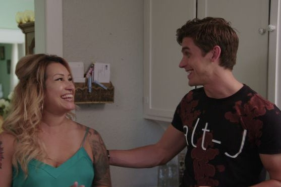 Antoni from 'Queer Eye' putting his hand on Deanna's shoulder as they both smile and laugh.