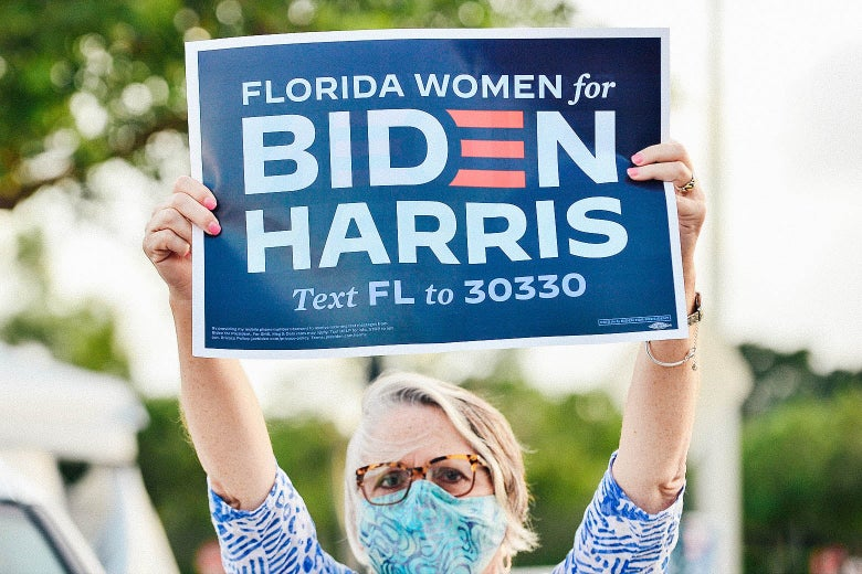 "A white woman in glasses and a face mask holds up a sign that says, ""Florida women for Biden Harris."""