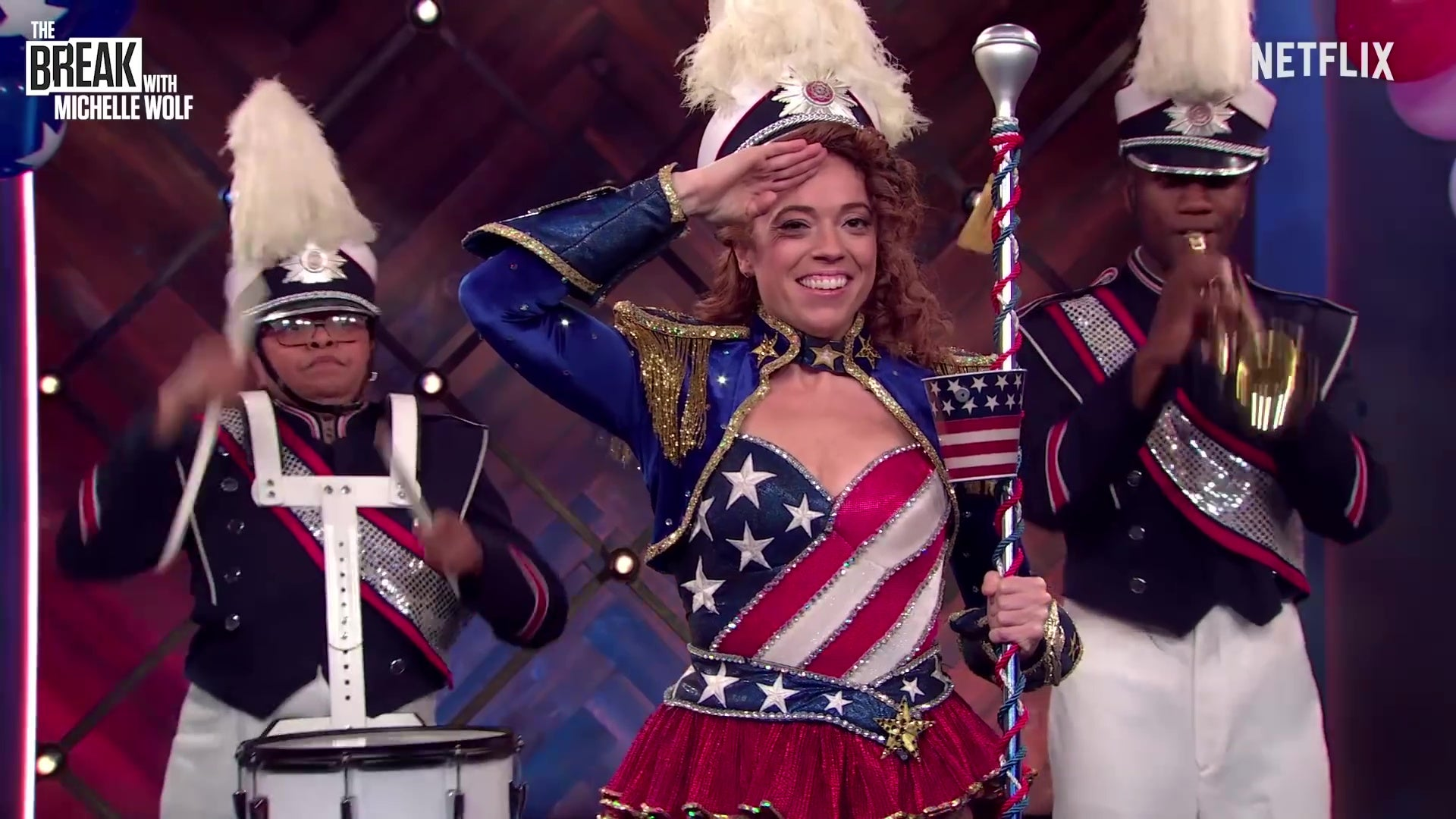 Michelle Wolf, dressed in red, white, and blue, salutes abortion as a marching band plays behind her.