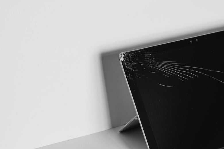 A tablet with a broken screen propped up on a stand.