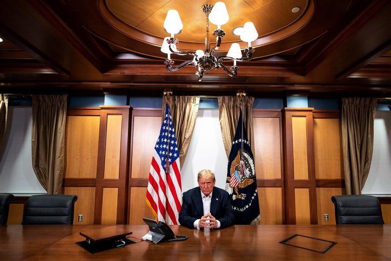 Trump sits hands clasped at a large conference room table with a speaker phone near him.