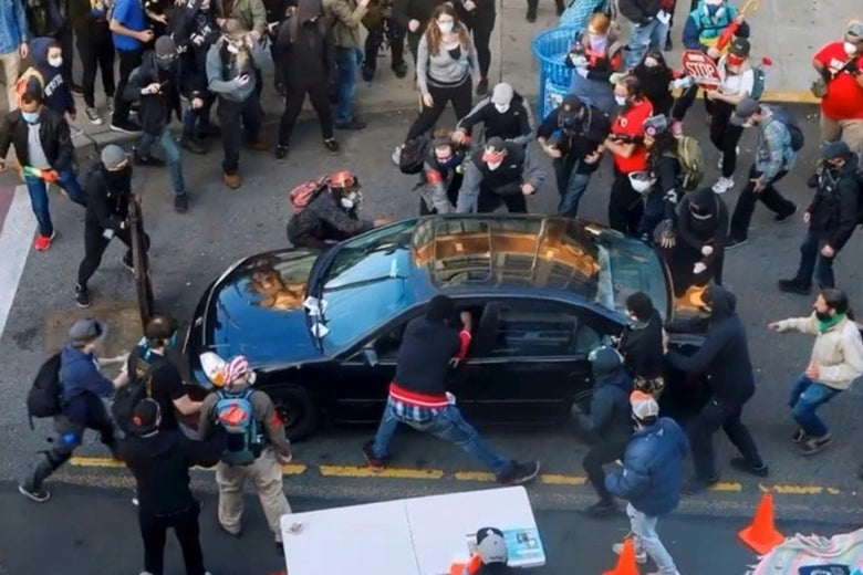 A crowd of protesters surrounds a car.