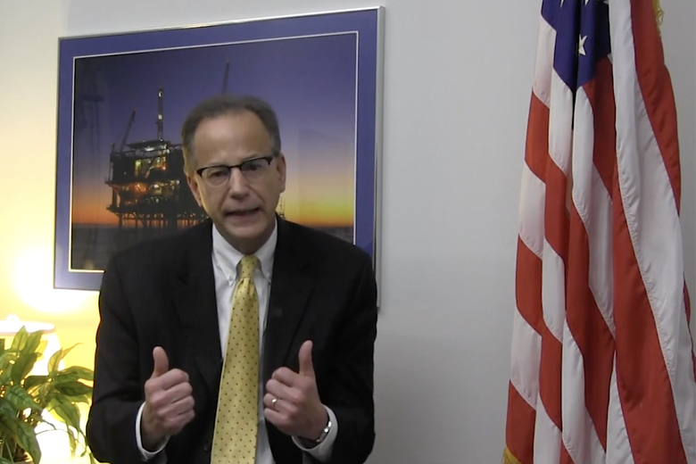 Scott Angelle gives a thumbs=up in front of photo of an oil rig