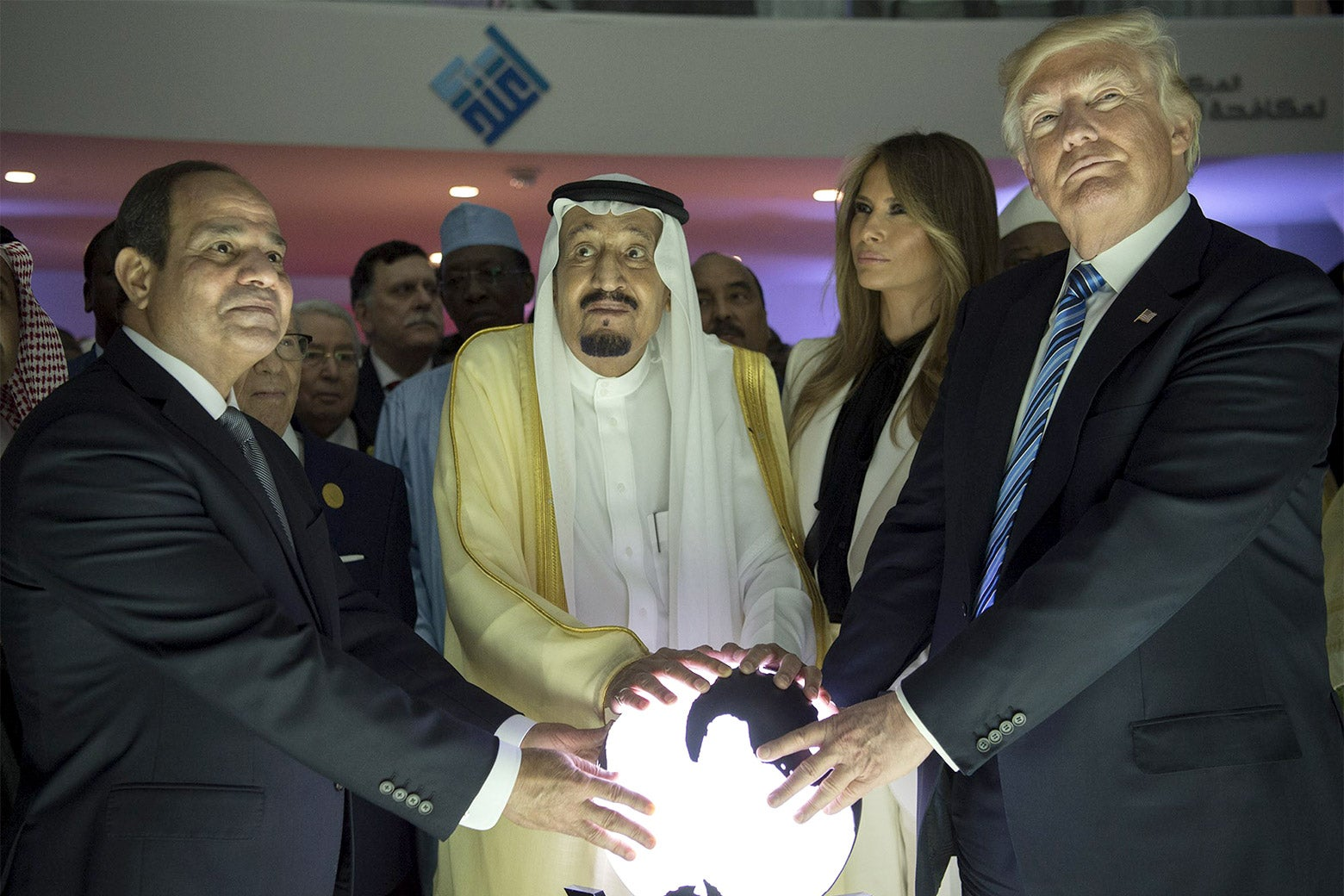 Trump, Sisi, and King Salman place their hands on an orb.