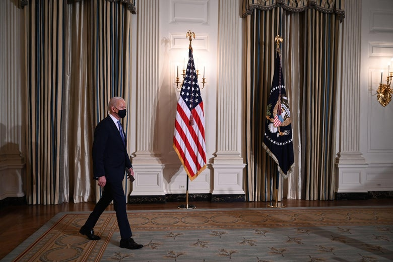 Joe Biden walks into a room in the White House with an American flag.