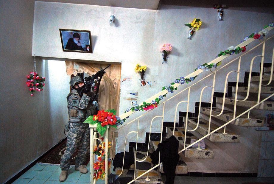 Staff Sgt. Zebadiah Thomas, of C Co., 3MUSSAYYIB, Iraq—Staff Sgt. Zebadiah Thomas, of C Co., 3-7 Infantry, watches a stairwell as his squad checks the rest of the house for a fleeing suspect, March 9, 2008.-7 Infantry, watches a stairwell as his squad checks the rest of the house for a fleeing suspect in Musayyib, Iraq, March 9, 2008.
