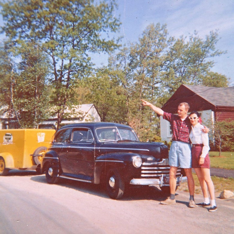 Jim and Carol stand in front of a black car. Jim points up and to the left.